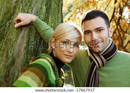 Closeup outdoors portrait of young couple smiling at camera at tree trunk.? - stock photo