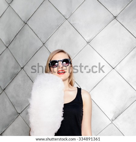 Closeup outside portrait of naughty young blonde girl having fun on the street. Posing with cotton candy near gray wall. Wearing sunglasses  - stock photo