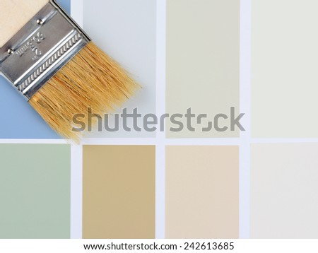 Closeup overhead shot of a paint brush laying on a color sample chart. Vertical format with the brush in the upper left corner, with copy space. - stock photo
