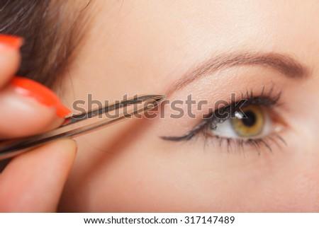 Closeup part of face, woman plucking eyebrows depilating with tweezers. Girl tweezing eyebrows. - stock photo