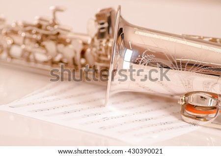 Closeup partly view of shiny saxophone lying on musical notes paper - stock photo