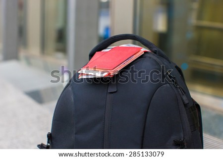 Closeup passports and boarding pass on backpack at airport - stock photo