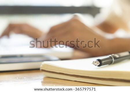 Closeup pen and blur bokeh working hands of asian businesswoman  - stock photo