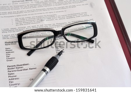 Closeup pen on receipts with eyeglasses