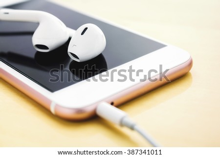 closeup phone and earbud on wood desk