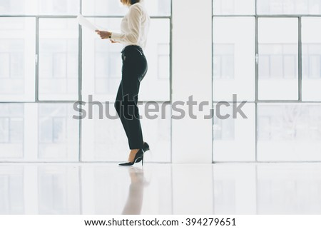 Closeup photo business woman wearing suit. Open space loft office. Holding papers hands. Analyze plans, meeting, panoramic windows background. Horizontal mockup.