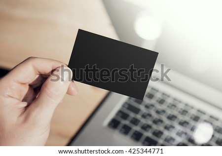 Closeup Photo Man Showing Blank Craft Business Card and Using  Modern Laptop Blurred Background. Mockup Ready for Private Information. Sunlight Reflections Screen Gadget. Horizontal mock up