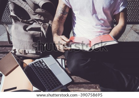 Closeup photo man wearing white tshirt sitting city park and reading book. Studying at the University,  preparation for exams. Books, generic design laptop, backpack bench. Horizontal, film effect - stock photo