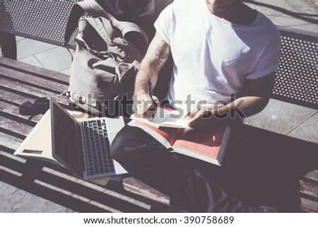 Closeup photo man wearing white tshirt sitting city park and writing notebook. Studying at the University,  preparation for exams. Books, generic design laptop, backpack bench. Horizontal, film effect - stock photo