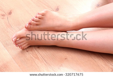 Closeup photo of a beautiful female feet with red pedicure - stock photo