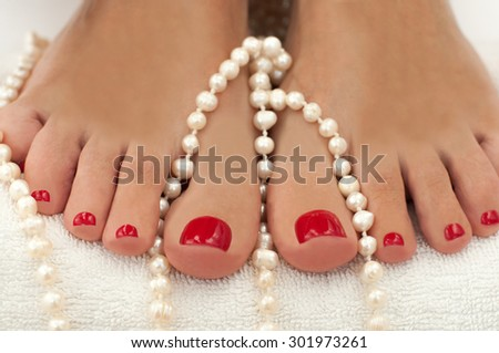 Closeup photo of a beautiful female feet with red pedicure isolated on white and decorated with pearls