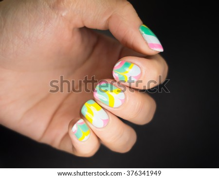 Closeup photo of a beautiful female hands with color nails - stock photo