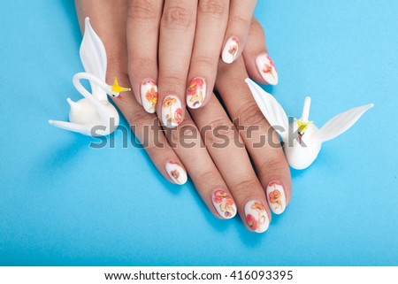 Closeup photo of a beautiful female hands with manicure on a blue background - stock photo
