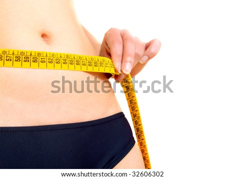 Closeup photo of a Caucasian woman's abdomen and breasts. She is measuring her waist with a yellow metric tape measure after a diet. - stock photo