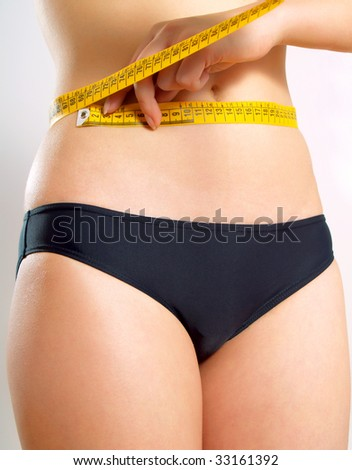 Closeup photo of a Caucasian woman's abdomen. She is measuring her waist with a yellow metric tape measure after a diet. - stock photo