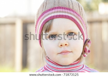 Closeup photo of a cute toddler girl with a knit hat