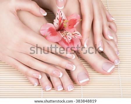 Closeup photo of a female feet at spa salon on pedicure and manicure procedure - Soft focus image - stock photo