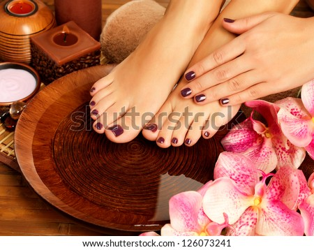 Closeup photo of a female feet at spa salon on pedicure procedure. Female legs in water decoration  the flowers. - stock photo