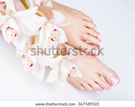 Closeup photo of a female feet with white french pedicure on nails. at spa salon. Legs care concept - stock photo