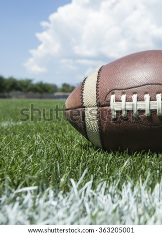 Closeup photo of a football resting on an outdoor field - stock photo