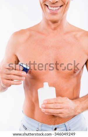 Closeup photo of a handsome shaved man opening a bottle of lotion
