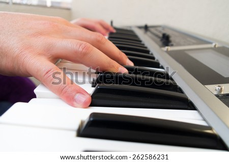 closeup photo of a musician's hands playing piano side view