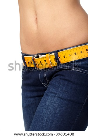 Closeup photo of a slim woman's abdomen and jeans with measuring tape instead of a belt.