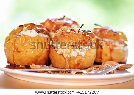 Closeup photo of a tasty baked apples stuffed with cheese cream, flavored with cinnamon, nuts and honey, served on the plate with a silver spoon, healthy nutrition, delicious fruit dessert - stock photo