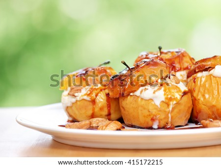 Closeup photo of a tasty baked apples stuffed with cream honey and nuts, healthy nutrition, delicious sweet food, gorgeous fruit dessert flavored with cinnamon - stock photo