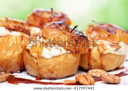 Closeup photo of a tasty baked apples stuffed with cream honey and nuts, healthy nutrition, delicious sweet food, gorgeous fruit dessert flavored with cinnamon