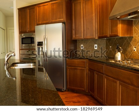 Closeup photo of a walkway behind Kitchen Island with stainless steel appliances, gas stove, stone counter tops and cherry wood cabinets with hardwood floors