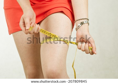 Closeup photo of a woman's leg. She is measuring her thigh with a yellow tape measure after a diet  - stock photo