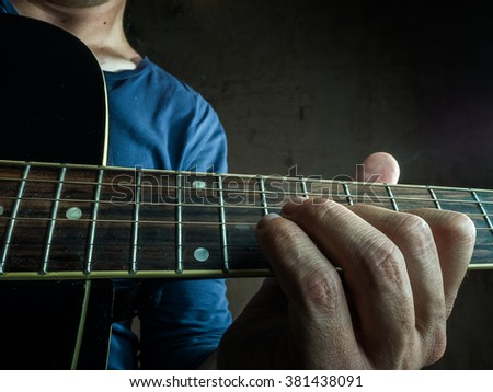 Closeup photo of an acoustic guitar played by a man. Only hands and body are visible. Unrecognizible guitar player. - stock photo