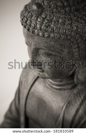 Closeup photo of antique wooden statue taken from above; shallow depth of field with focus on downcast eye - stock photo