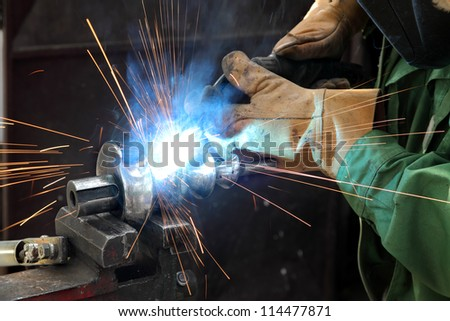 Closeup photo of arc welding of a steel shaft with helicoid - stock photo