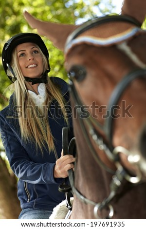 Closeup photo of attractive female rider on horseback. Photographed from below. - stock photo
