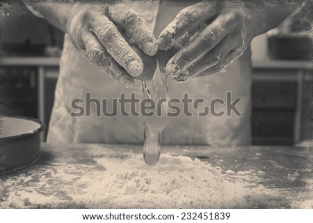 Closeup photo of baker cracking egg for dough. Retro styled imagery.