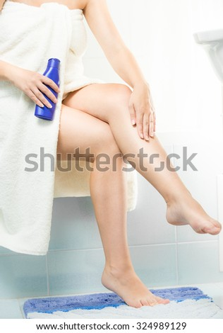 Closeup photo of beautiful woman applying moisturizing creme after shaving legs - stock photo
