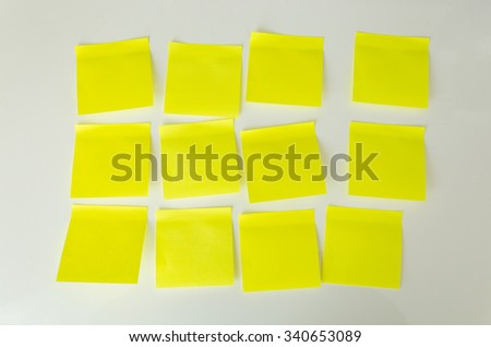 Closeup photo of 12 blank yellow sticky notes on white board - stock photo