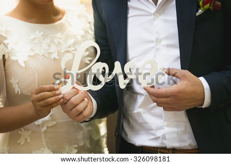 Closeup photo of bride and groom holding word Love - stock photo