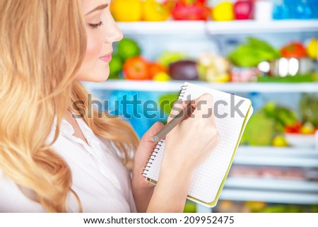 Closeup photo of cute blond housewife writing list to go to supermarket,colorful vegetables and fruits fridge shelves, healthy nutrition concept - stock photo