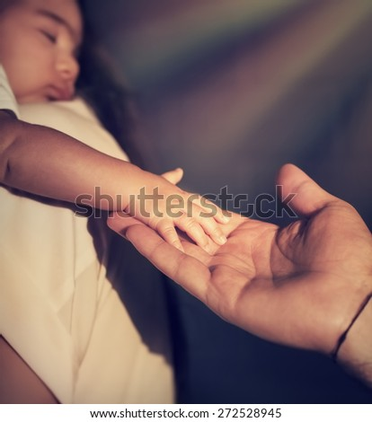 Closeup photo of cute little baby on mothers hands touching fathers hand, bright sun rays shining as a blessing of God, hope and protection concept - stock photo