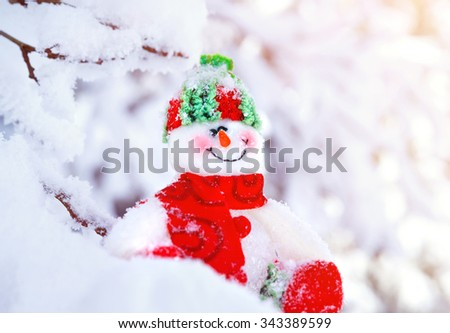 Closeup photo of cute little snowman toy sitting in the snow outdoors, traditional symbol of winter, happy Christmas holidays - stock photo