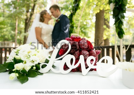 "Closeup photo of decorative sign ""Love"" on table at wedding ceremony - stock photo"