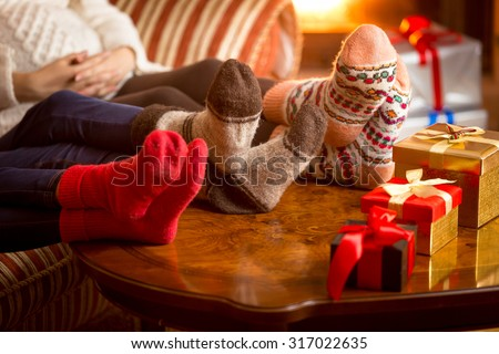 Closeup photo of family's legs in woolen socks next to fireplace at Christmas - stock photo