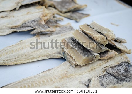 Closeup photo of fish market stand with piles of salty fish and white plastic containers - stock photo