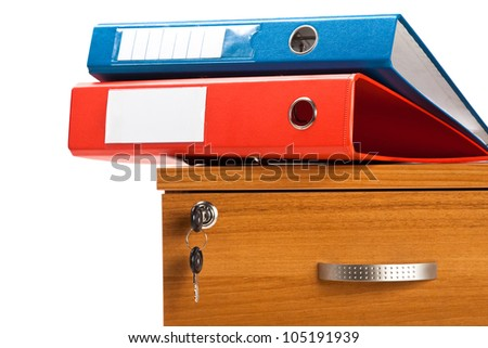 Closeup photo of 2 folders laying on cabinet with keys on white background