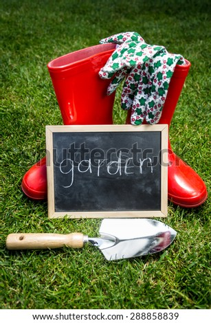 "Closeup photo of garden tools and blackboard with word ""Garden"" on green grass - stock photo"