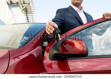 Closeup photo of handsome car salesman giving keys - stock photo