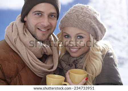 Closeup photo of happy loving couple drinking tea at wintertime outdoors. - stock photo
